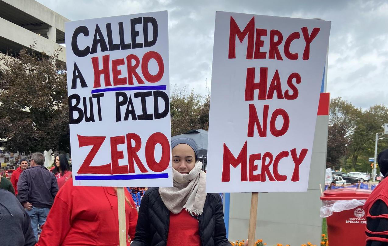 CWA member holding a sign saying Mercy Has No Mercy