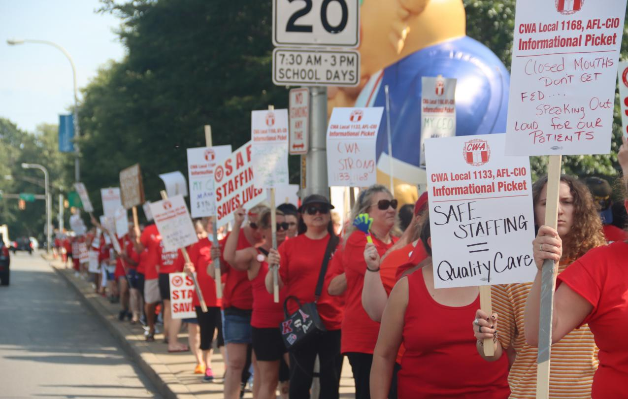 Picture of August 25 Info Picket at Mercy Hospital with dozens of people marching holding signs